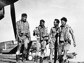 Four men in military flying gear walking among single-engined aircraft on an airfield