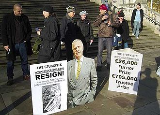 The Upper Room (paintings) - Outside the Turner Prize, Tate Britain, 2005: Stuckists demonstrate against the purchase of Chris Ofili's The Upper Room. The cutout is Tate Chairman Paul Myners.