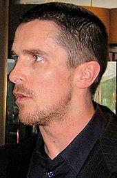 Profile shot of a man looking to his left. He has a goatee and stubble, and is wearing a black dress shirt with collar and a black blazer.