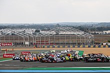 A plethora of cars turning left into a corner at the Circuit de la Sarthe