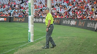 Umpire (Australian rules football) - A goal umpire officiating between the goal posts at one end of the football field.
