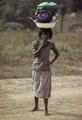 ASC Leiden - F. van der Kraaij Collection - 01 - 067 - A woman in a nice dress is standing, her hand on the chin wearing earrings - Voinjama, Lofa County, Liberia, 1976.tiff