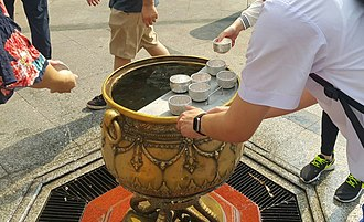 Holy water - A Thai student pouring the holy water on his two hands at Erawan shrine, Bangkok