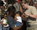 A U.S. Airman Helps Put Ear Plugs in the Ears of an Infant in Port-au-Prince, Haiti.jpg