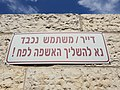 A sign with a request in Hebrew to be sure to throw the garbage into the container.jpg