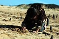 A young girl attentively admires her recently dug hole where she will place a coastal dune plant. (32297813503).jpg