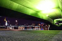 Ak Ignatz-Bubis-Brücke und Frankfurter Skyline unter der Flößerbrücke bei Nacht.jpg