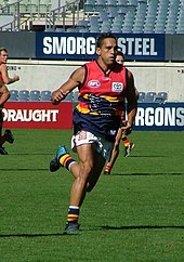 A male athlete with dark hair wearing a sleeveless jersey and shorts runs on the grass surface of the playing arena.