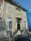 foto van Dubbel huis met drieraams zandstenen gevel van zeer monumentale verhoudingen, onder rechte lijst met triglyfen, consoles en door beelden bekroonde attiek