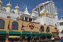 The facade of the Trump Taj Mahal, a casino in Atlantic City. It has motifs evocative of the Taj Mahal in India. A tall building with the resort's name stands in the background.
