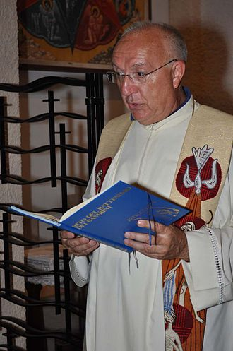 Catholicity - An Italian priest during the sacrament of Baptism