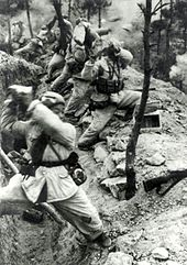 A line of soldiers are standing in front of a trench and holding rocks over their shoulders. Rocks are flying to the right while smokes are filling the background.