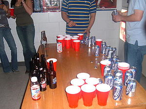 Drinking game - Beer pong is a drinking game in which players throw ping pong balls across a table, attempting to land each ball in a cup of beer on the other end