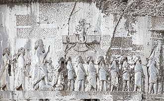 Behistun Inscription - Punishment of captured impostors and conspirators: Gaumāta lays under the boot of Darius the Great. The last person in line, wearing a traditional Scythian hat and costume is identified as Skunkha. His image was added after the inscription was completed, requiring some of the text to be removed.