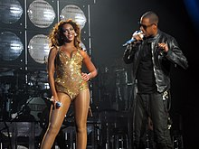 Two people are performing on stage. The woman, at left, wears a pink short dress, transparent stockings, and holds a microphone with her right hand. She is looking something at her right while she holds her left on her hip. The man is talking through a microphone. He wears dark clothes (a jacket, a shirt and pants).