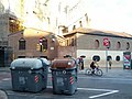 Brick building, trash bins, and bikeway in front of the Sagrada Familia (18602128458).jpg