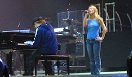 Image of a blond female performer. She is wearing blue jeans and a sleeveless light blue top, she is standing next to a piano player, who is playing a big black piano. Her left hand is in her hip while her right hand holds her mic while she is singing. Two members of the crew stand a few meters behind them.