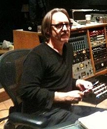 A man wearing glasses and black clothes sits in the control room of a recording studio.