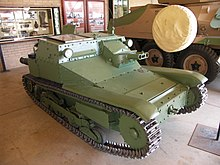 a green turret-less tracked vehicle inside a  building
