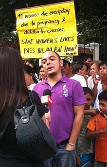A photograph of a broadcast journalist holding a microphone to Carlos Celdran as he speaks in an interview. A crowd of demonstrators stand behind him, one holding a sign which reads