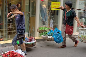 Carrying pole - Two Chinese women using carrying poles to transport produce Nanjing, China.