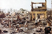 A number of Asian civilians standing amid ruined buildings and rubble.