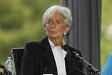 A[permanent dead link] three-quarter portrait of an elegantly dressed Christine Lagarde, perhaps in her early 60s sitting in a chair behind a microphone. She looks fit and tanned. Her overall mien is alert, pleasant, and intelligent.