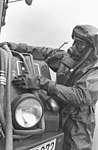 DF-SN-84-06878 A West German soldier, wearing Nuclear, Biological, and Chemical gear, winds up a hose in 1978.jpeg