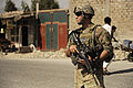 Defense.gov News Photo 110926-F-RN211-119 - U.S. Army Spc. Alexander Oliveira provides security at an intersection while Afghan Uniformed Police lead the way on a joint patrol in Mehtar Lam.jpg