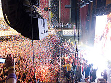 Confetti falling on a packed theater as many people on stage wave to audience.