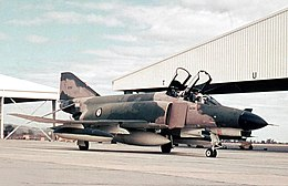 Two-seat military jet fighter painted in camouflage livery with open canopies, parked at airfield