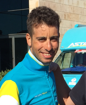 A photograph of Fabio Aru in front of an Astana team vehicle