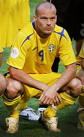 A soccer player in yellow shirt and yellow shorts squating for a photo.