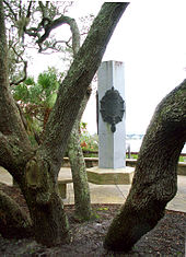 A cement monument, a pentagon-shaped column with bronze plaques adorned with the fleur-de-lis, surrounded by oak trees in the foreground, palmettos to the left all overlooking the river