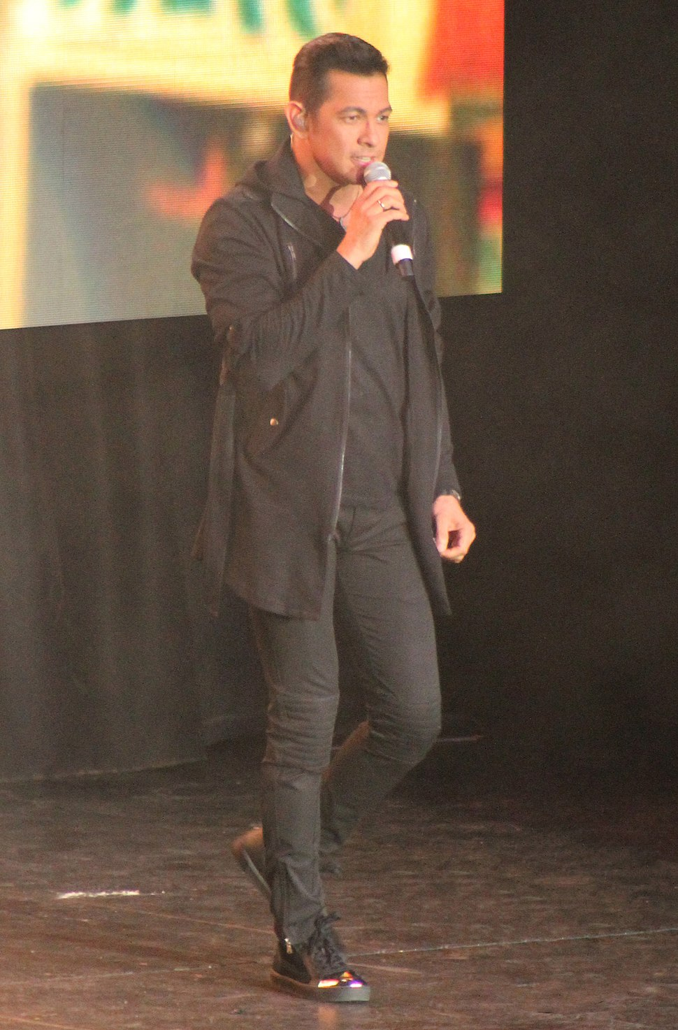 A full body image of Valenciano wearing black pants, shirt, jacket and sneakers while singing into a hand-held microphone