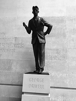 "George Orwell statue at the headquarters of the BBC. A defence of free speech in an open society, the wall behind the statue is inscribed with the words ""If liberty means anything at all, it means the right to tell people what they do not want to hear"", words from George Orwell's proposed preface to Animal Farm (1945).[80]"