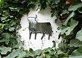 Glasierter keramischer Osborne-Stier, umhüllt von rankendem Efeu auf einer weißen Außenfassade.jpg