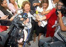 A distraught woman talks into a microphone with her eyes closed, surrounded by reporters. On the front of the woman's white t-shirt there is a printed color portrait of a smiling man. Next to her stands a younger woman with her head down.