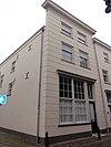 foto van Huis op de hoek van de St.Jorisstraat, met gebosseerd grijsgepleisterde lijstgevel en zadeldak