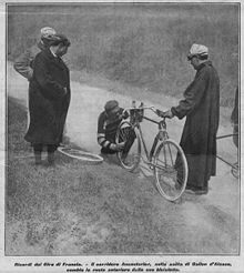 A man working on the front tire of a bicycle; three men are watching.