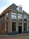 Ten dele onderkelderd hoekpand met verdieping en rechte kroonlijst onder schilddak met voordeur en dakkapel in Lodewijk XVI-/Empirestijl