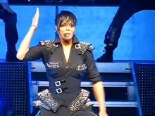 A woman on a stage, wearing dark clothing and a microphone; one of her arms is at her side while the other is extended into the air.