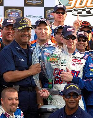 Jeff Burton - Stephen Rochon and Jeff Burton hold the victory trophy from the 2006 Nicorette 300