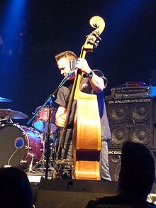 An upright bass player, Jimbo Wallace, performs onstage with his bass plugged into a large Gallien-Krueger bass stack and amplifier.