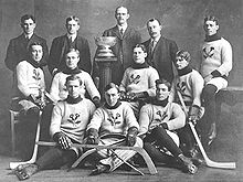 An early ice hockey team poses for a photo. Eight players, all seated around a trophy on a pedestal, are dressed in wool sweaters with a thistle emblem. They wear skates and hold ice hockey sticks. Behind them stand four men in suits.