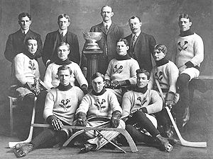 An early ice hockey team poses for a photo with a small championship trophy in the middle of them.
