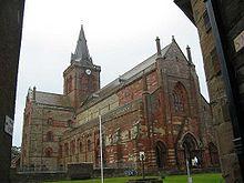 Une grande église en pierre rouge et jaune avec une tour carrée et une flèche sur la tour.