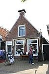 foto van Eenvoudige woning met geprofileerde kozijnen en aanzetlijsten onder zadeldak tegen topgevel