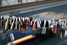 """Love locks"" on the Brooklyn Bridge. Couples inscribe a date and their initials onto a lock, attach it to the bridge, and throw the key into the water as a sign of their love."