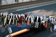 """""""Liebesschlösser"""" auf der Brooklyn Bridge.  Paare schreiben Datum und Initialen auf ein Schloss, befestigen es an der Brücke und werfen den Schlüssel als Zeichen ihrer Liebe ins Wasser."""